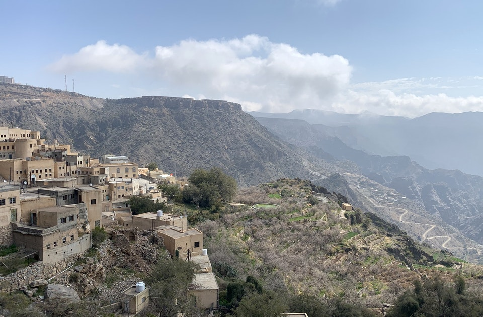 Von Weitem kaum als Hotelanlage zu erkennen – Oberhalb eines gewaltigen Canyons liegt das Anantara Al Jabal Al Akhdar Resort auf einem Plateau, behutsam in die Natur integriert (im Hintergrund), vorne das fast vollständig verlassene Bergdorf Ash Shirayjah