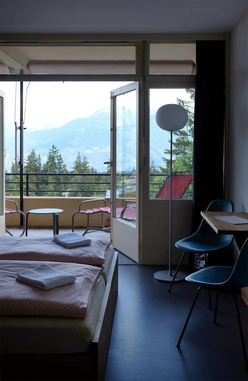 Süd-Zimmer mit Aussicht: Zeitlose Holzmöbel, Bettwäsche im Retro-Design, Linoleumboden, Stühle von Vitra und Original-Liegen von 1929 auf dem tiefen Balkon