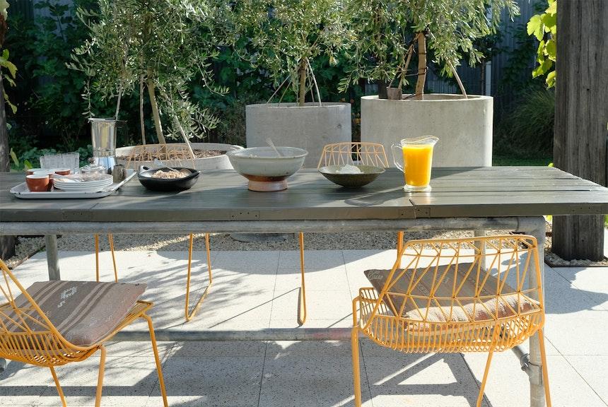 Olivenbäume, ein altes Türblatt als Tisch und Terrazzofliesen