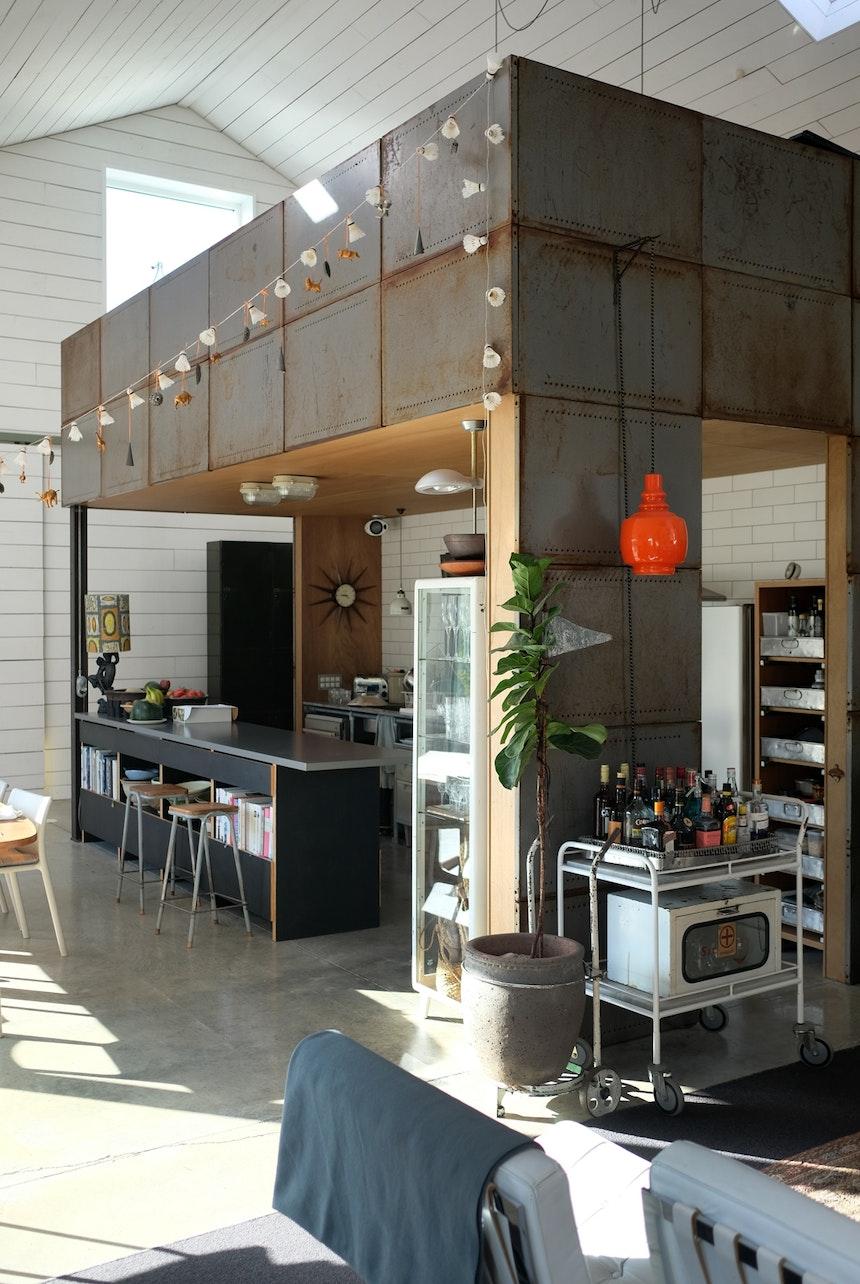 Korpus aus Holz und rostigen Regal-Einlegeböden aus Stahl, unten Küche, oben Officebereich