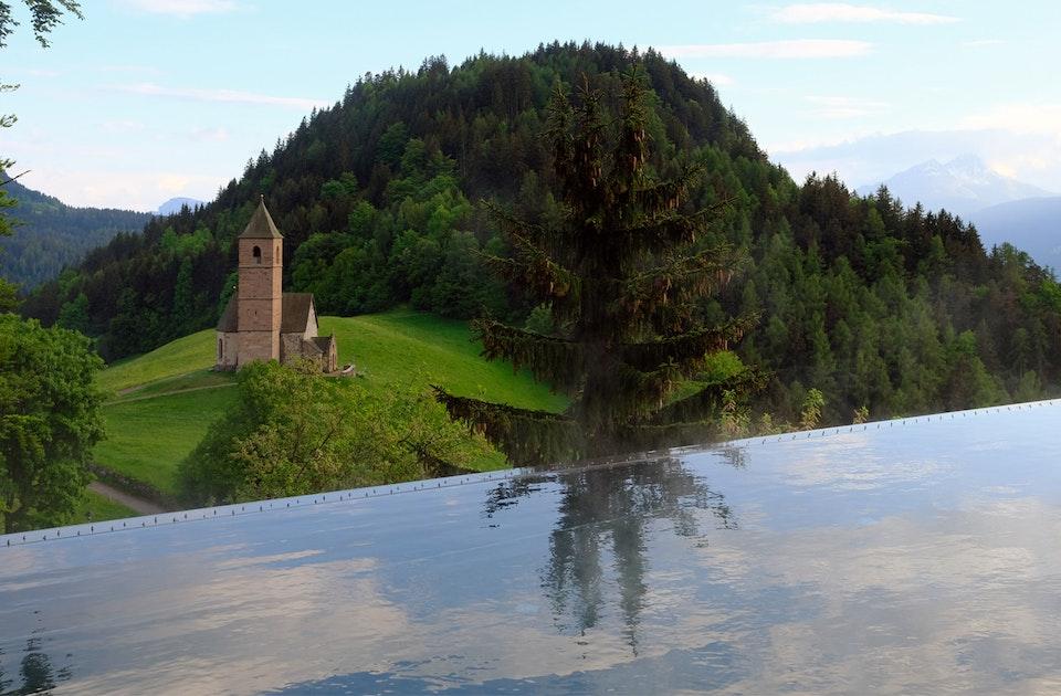 Schwimmen mit Sicht auf Wiesen, Wälder, Berge und die Kirche von Hafling