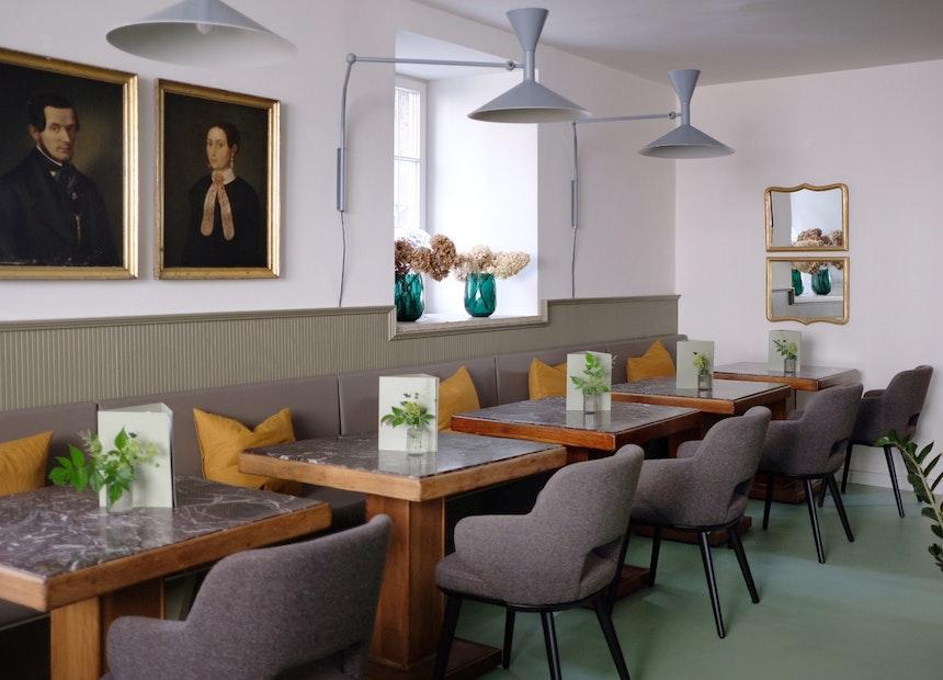 Im Townhouse Bistro finden die alten Tische eines Mailänder Bahnhofs einen neuen Platz, Le Corbusiers Leuchten »Lamp de Marseille« (Nemo Lighting) sorgen für gemütliche Beleuchtung, Portraits eines lokalen Antiquitätenhändlers leisten beste Gesllschaft