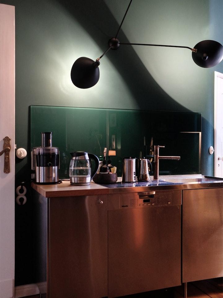 Das Glas hinter der Küchenzeile wurde auf der Rückseite in der Wandfarbe gestrichen