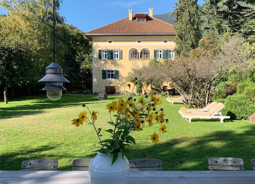 Blumendekoration passend zu den Gartenmöbeln – Rudbeckien (Sonnenhut) in weißen Tonvasen, Pendelleuchte Santorini von Sputnik Studio für Marset