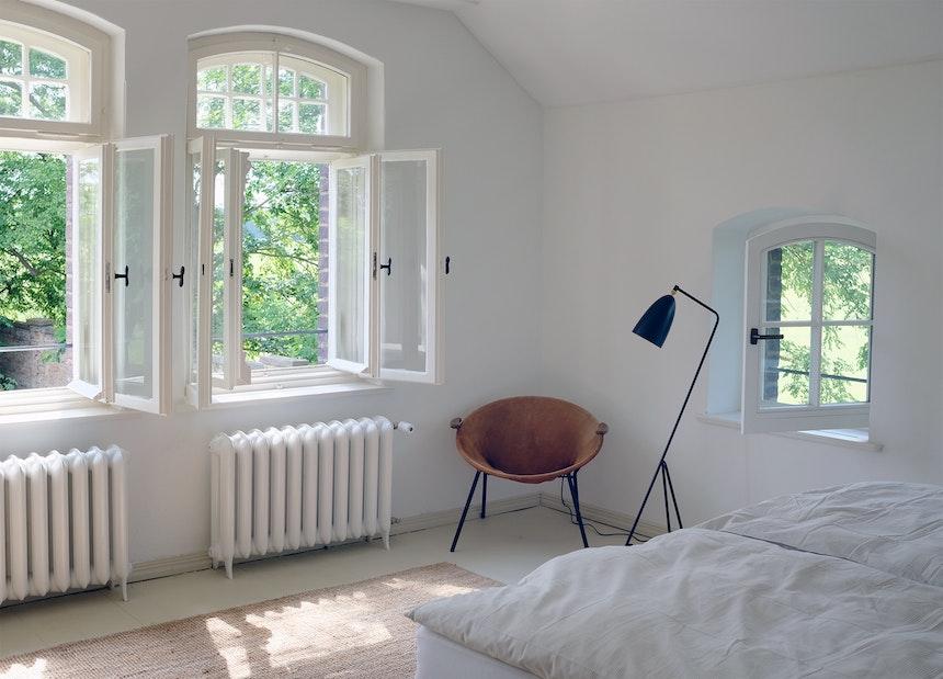 Die insgesamt vier Schlafzimmer der Villa wurden bewusst hell, leicht und fein eingerichtet, Lampe von Gubi, Sessel Vintagefund