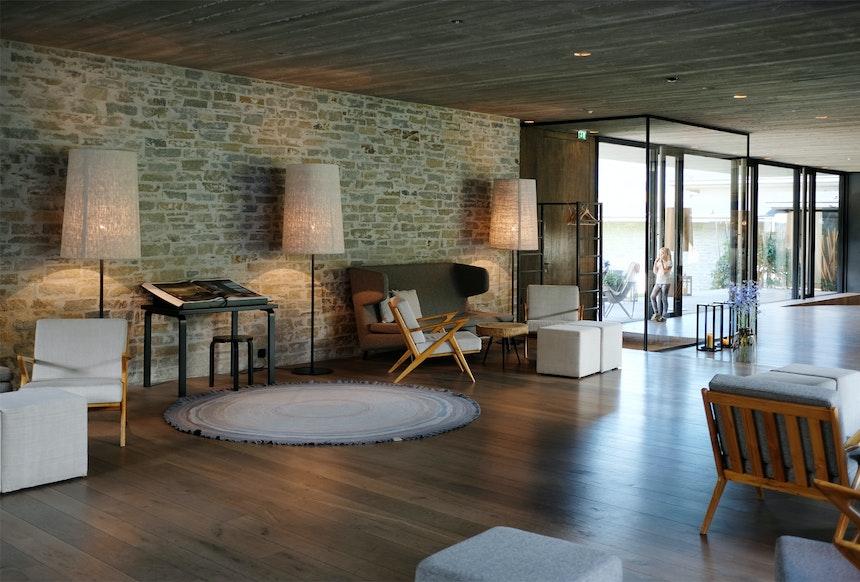 Lobby mit Rezeption – gestaltet mit Naturmaterialien in warmen Erdtönen