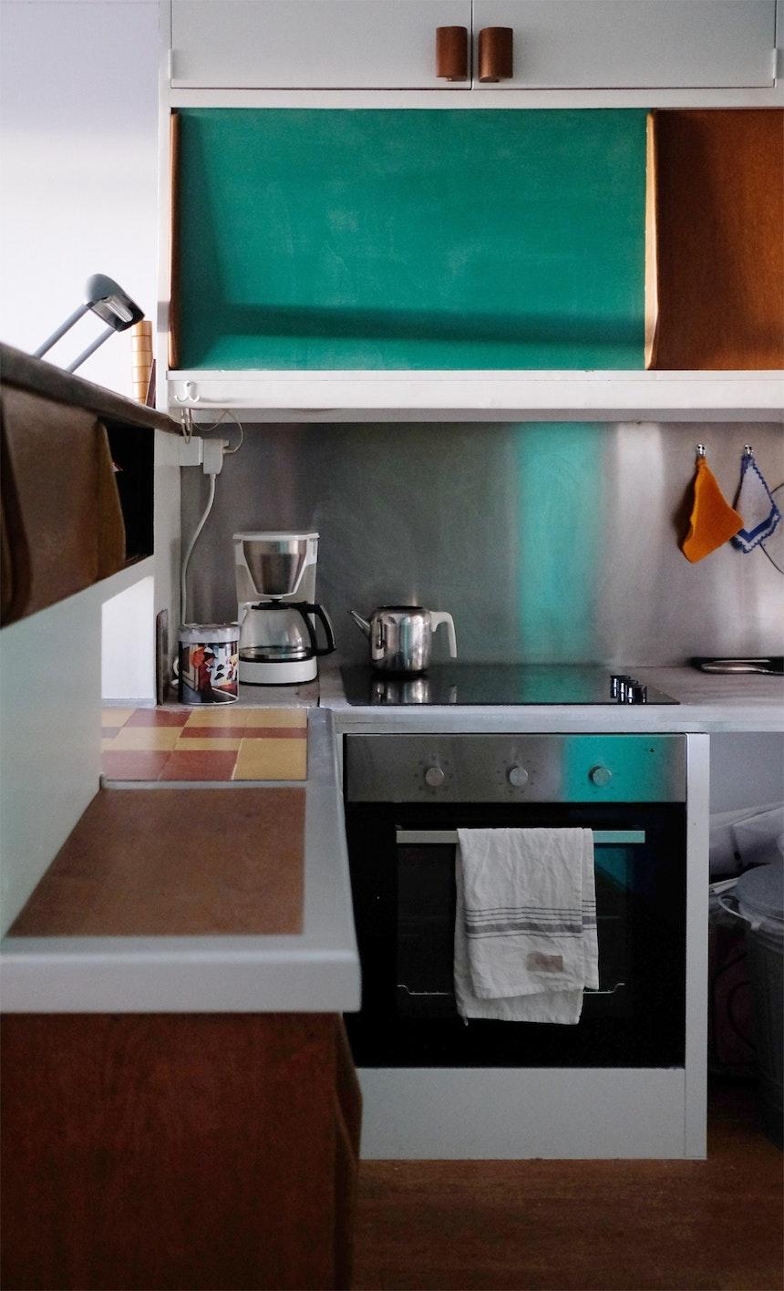 Schränke mit Schiebetüren und Griffen, die an Tragflächen eines Modellflugzeugs erinnern, Durchreiche, Holz und die Farbe Veroneser Grün bestimmen das Aussehen der kleinen Küche