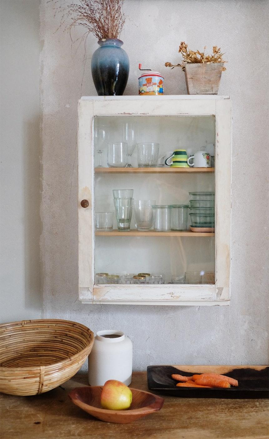 Küchen-Stilleben aus Flohmarktfund, unverputzter Wand und dekorativen Alltagsdingen
