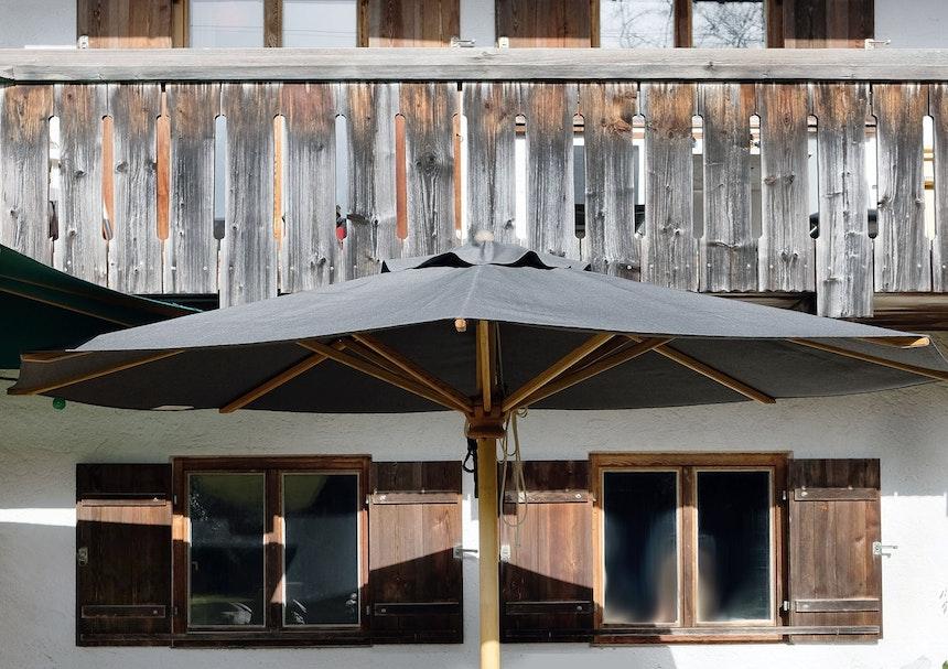 Vor Simons Elternhaus steht ein Chiemsee Schirm in Dunkelgrau – zur Zeit der Favorit der Kunden