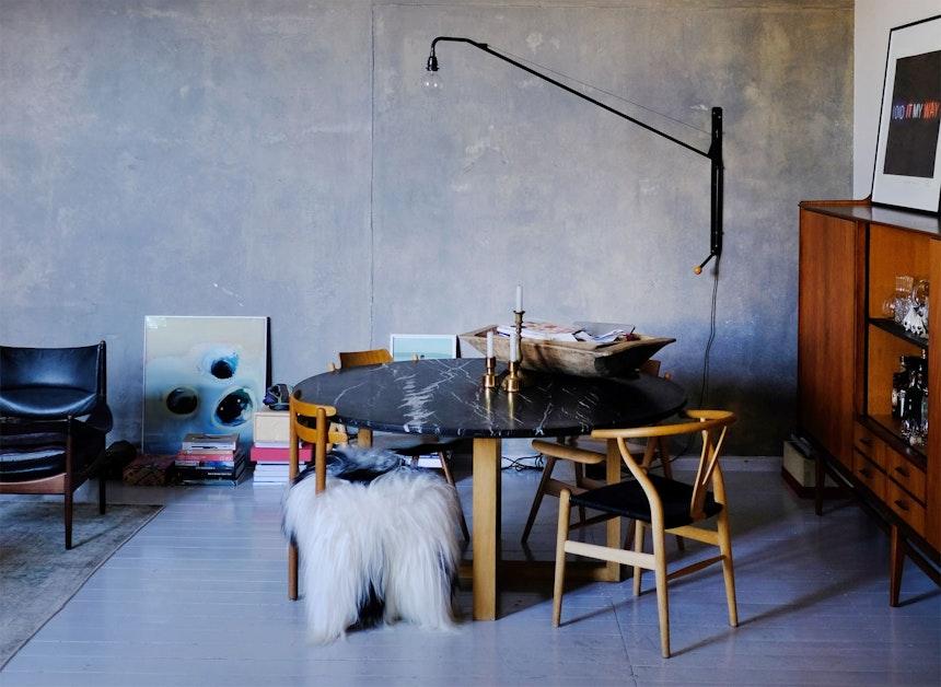 Blick aus der Küche in den Wohnbereich – Marmor, Beton, Teak & lackierte Holzdielen