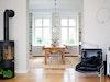Nach den Umbauarbeiten: Freier Blick bis in den Garten und mehr Licht, Wohn- und Essbereich werden zu einem großen Raum, der dänische Kaminofen (von Morsø) nimmt viel weniger Platz ein