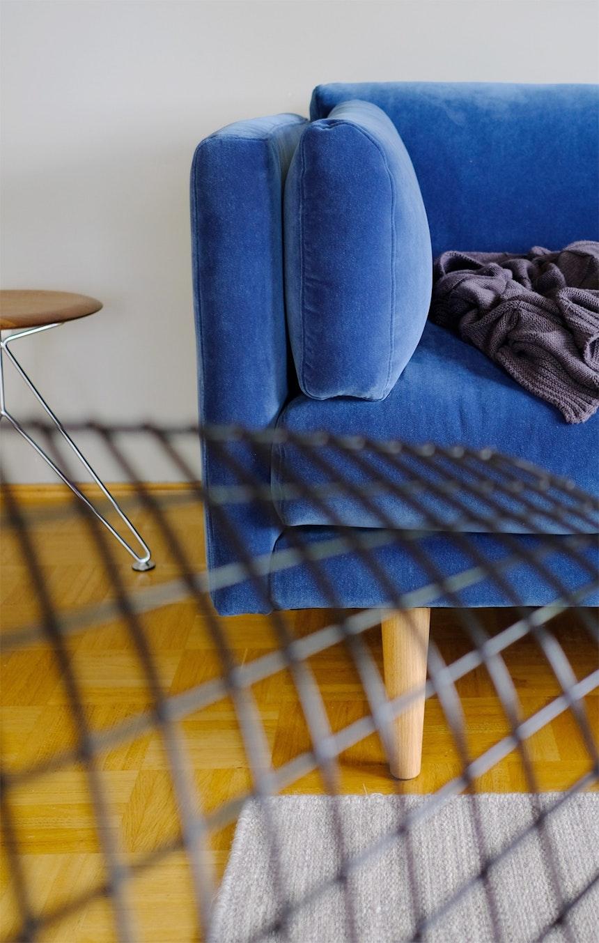 Blauer Samt, Eichenholz und ein gemütlicher Wollteppich, der sich optisch nicht aufdrängt