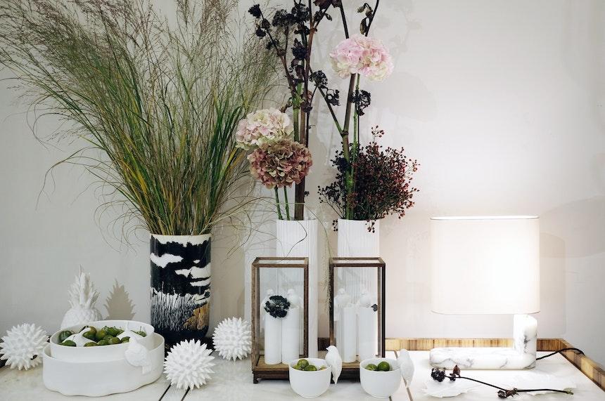 Weißes Porzellan, Marmorleuchte Columbo (CTO Lighting) und feine Blumendekoration im Showroom von Frank Stüve Interiors