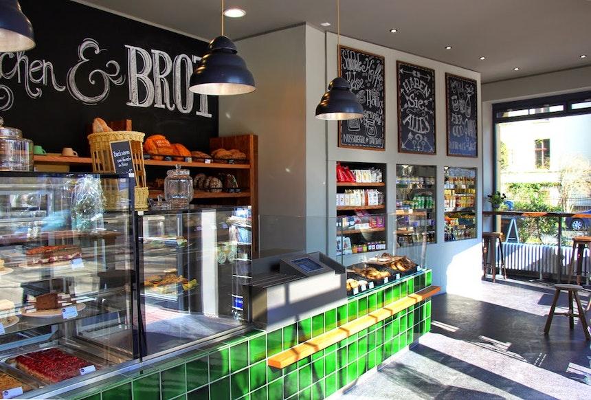 Bäckerei mit grün gekacheltem Tresen und Pendelleuchten ausSpitzenaufsätzen der Berliner Gaslaternen