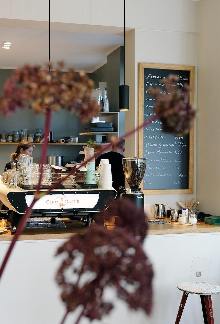 Durch die Blumendeko fotografiert – Die High End Kaffeemaschine SPIRIT von Kees van der Westen, nachhaltige RECUP Becher – Links im Hintergrund Küchenchefin Tonja