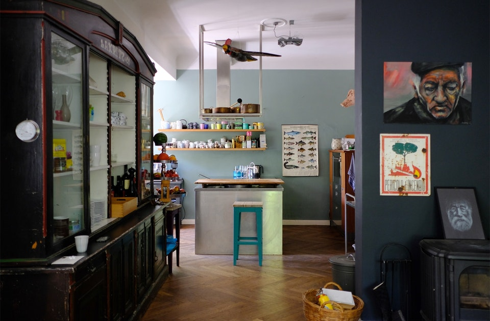 Coole Küche: Parkett, Kaufmannsregal, Arbeitsinsel aus Edelstahl, Barstuhl ARMSTRONG, Kupfertöpfe, Espressotassen-Sammlung, Fischposter, Filzschwein und aquablaue Wände