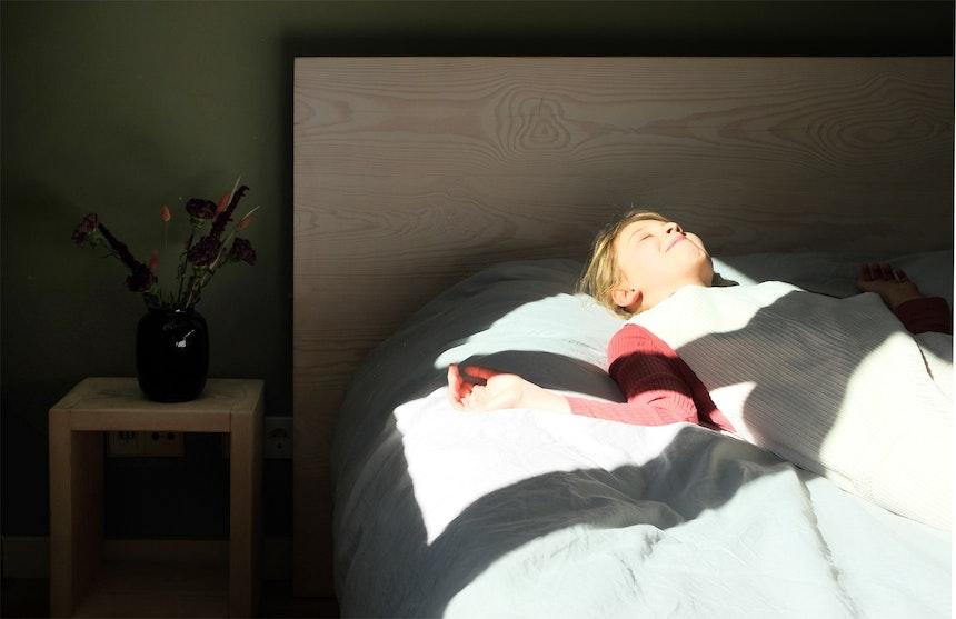Lies liegt im Gästezimmer-Bett AURONS und strahlt mit der Sonne um die Wette