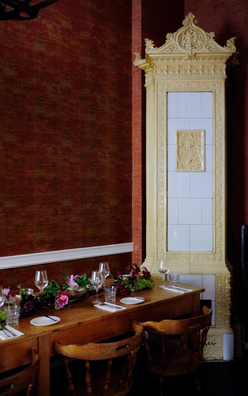 Im ehemaligen Tresorraum können bis zu 15 Gäste am alten Kachelofen Platz nehmen