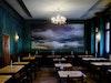 Warmes Petrol, Fischgrat-Parkett und alte Leuchter – Interior im Caféhaus-Stil