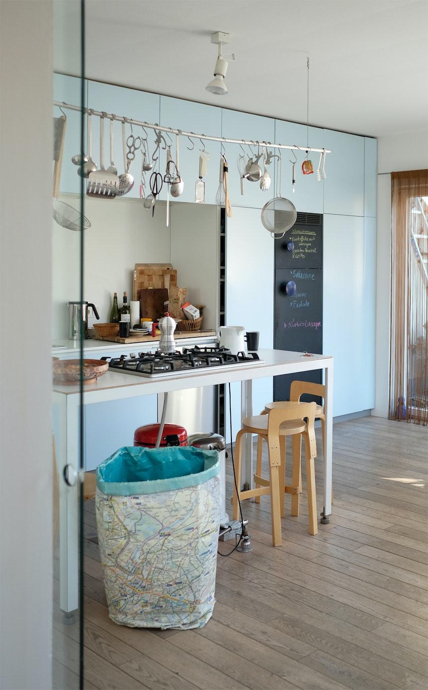 Blick in die himmelblaue Küche, Barstühle Artek K65, Design Alvar Aalto
