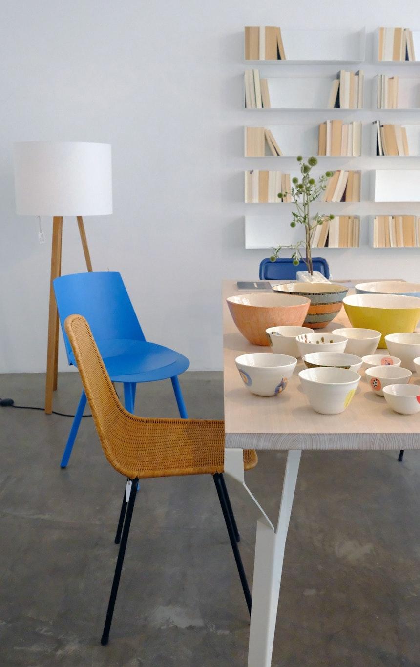 linea1 everyday table, linea1 a Taschenbuchregal, blauer Stuhl Houdini, Design: Stefan Diez für e15, davor Basket Chair, Design: Gian Franco Legler