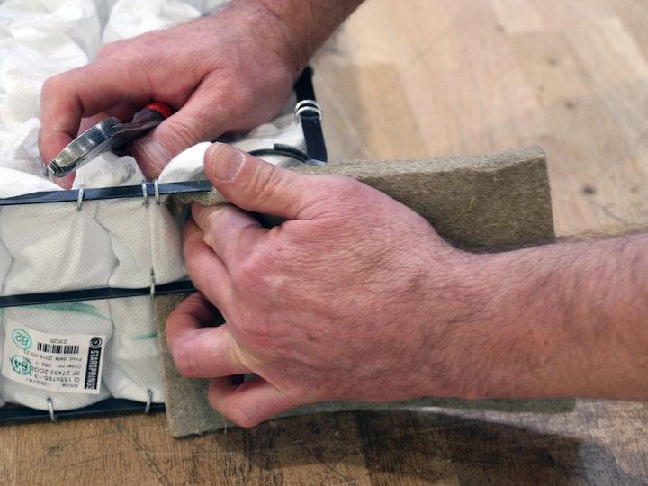 Der Metallrahmen wird mit Flachs/Leinen umspannt und von Hand vernäht