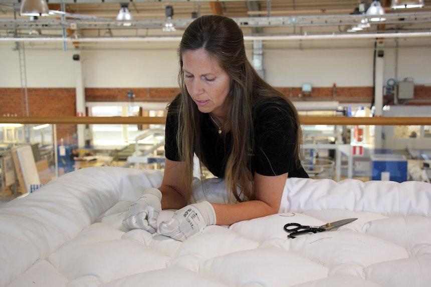 Petra Weiler, Näherin, beim Verknoten der Steppfäden