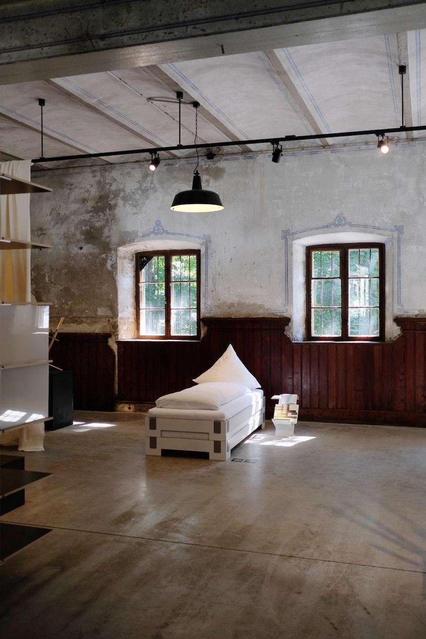 Ehemaliges Kutschenhaus: Bett »Tagedieb«, Design Carmen Buttjer, Beistelltisch »Liesmichl«, Design Nils Holger Moormann