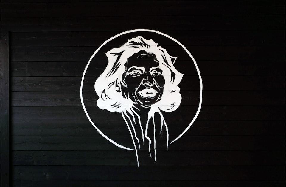 Amadeus' Großmutter Anthoula Tzamouranis, OEL-Logo auf dem Holztor des Büros im Weinbergsweg