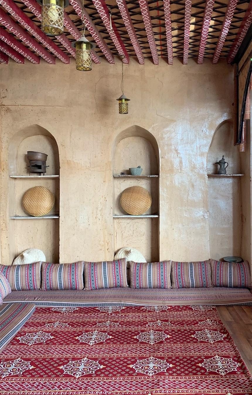 Omani Interieur – bemalte Deckenbalken, versiegelte Lehmwände (gegen den Staub), Sitzlandschaft auf dem Boden, traditionelle Stoffe und Teppiche & arabische Rundbögen