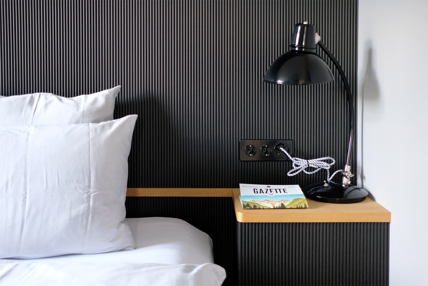 Zimmerdetails mit Bolichleuchte & Gazette – Die Hauszeitung, herausgegeben von Hotelchefin Franziska Richard, liegt in jedem Zimmer zum Lesen bereit und erscheint zwei Mal im Jahr
