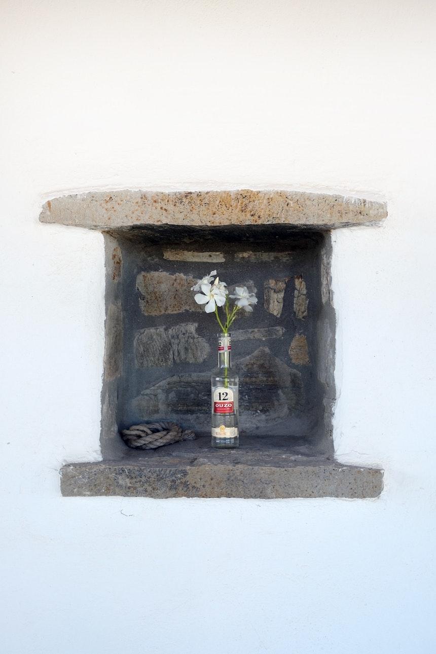 Recycle-Blumendeko im Ferienhaus – Oleander in der OUZO 12-Flasche