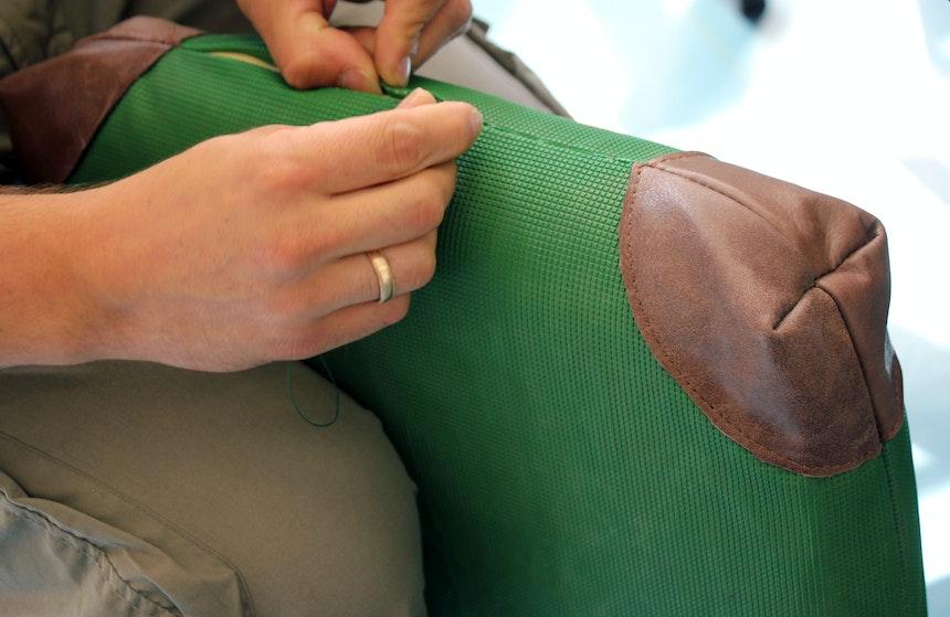 Das Sitzkissen aus einer alten Schulturnmatte wird von Hand genäht