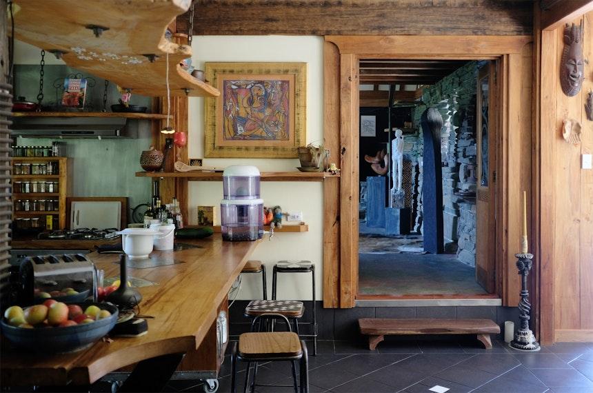Von der Eingangstür gelangt man in die offene Küche und den dahinter liegenden etwa 8 Meter hohen Wohnraum, der im Winter auch als Atelier genutzt wird