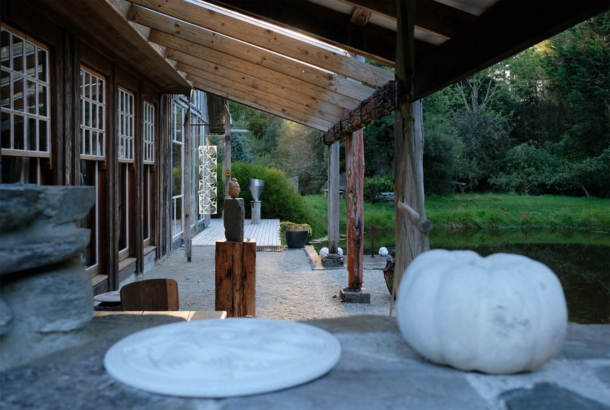 Blick über die Mauer auf eine der zahlreichen Sitzecken, Obstgarten, großen Teich und Skulpturen