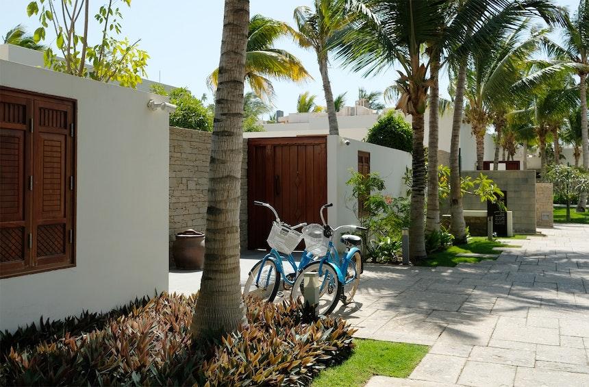 Angelegt wie ein südomanisches Dorf – 88 Villen in flacher, geometrische Bauweise, schwere Holztüren, von Kokospalmen gesäumte Wege, Fahrräder für die Gäste