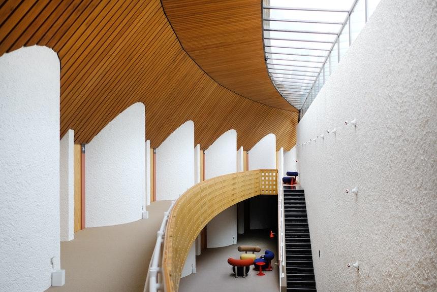 Offenes Treppenhaus mit geraden Treppenläufen und zum See ausgerichtete Zimmer – Hinter den halbrunden Mauern befinden sich die Bäder