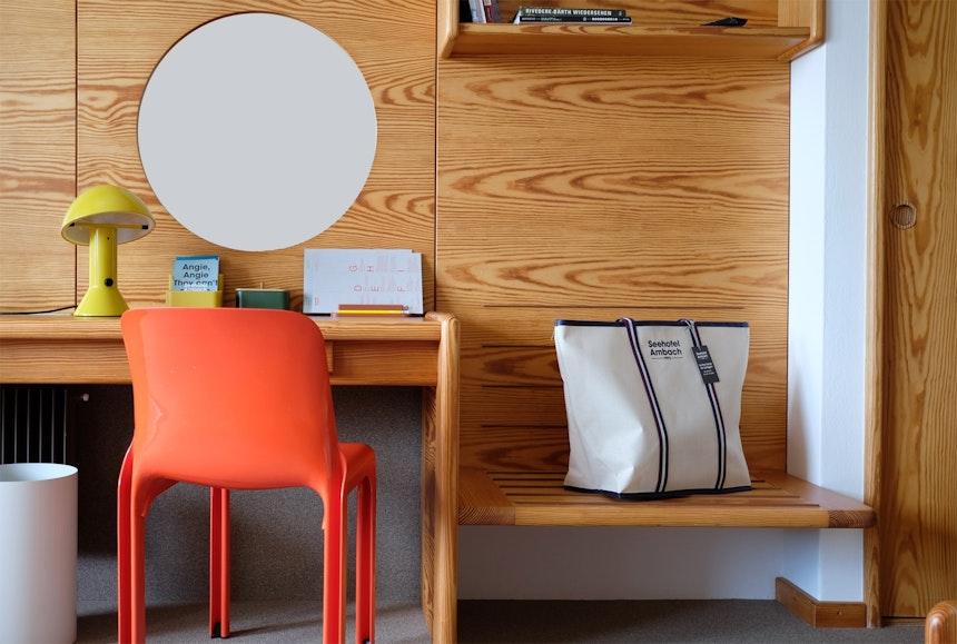 Schöner Stilbruch – Original-Einbauten aus Holz (Othman Barth), der Stuhl Selene von Nico Magistretti, 1969 für Artemide entworfen und die kleine gelbe Leuchte Elmetto, Design Elio Martinelli, 1976