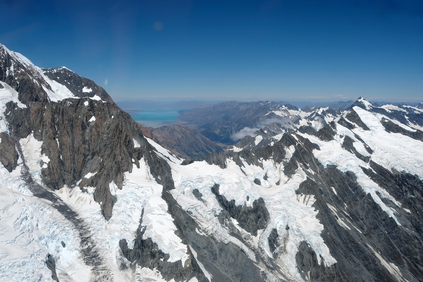 Vulkangestein, Gletscher und das türkisfarbene Wasser des Lake Tekapo im Hintergrund