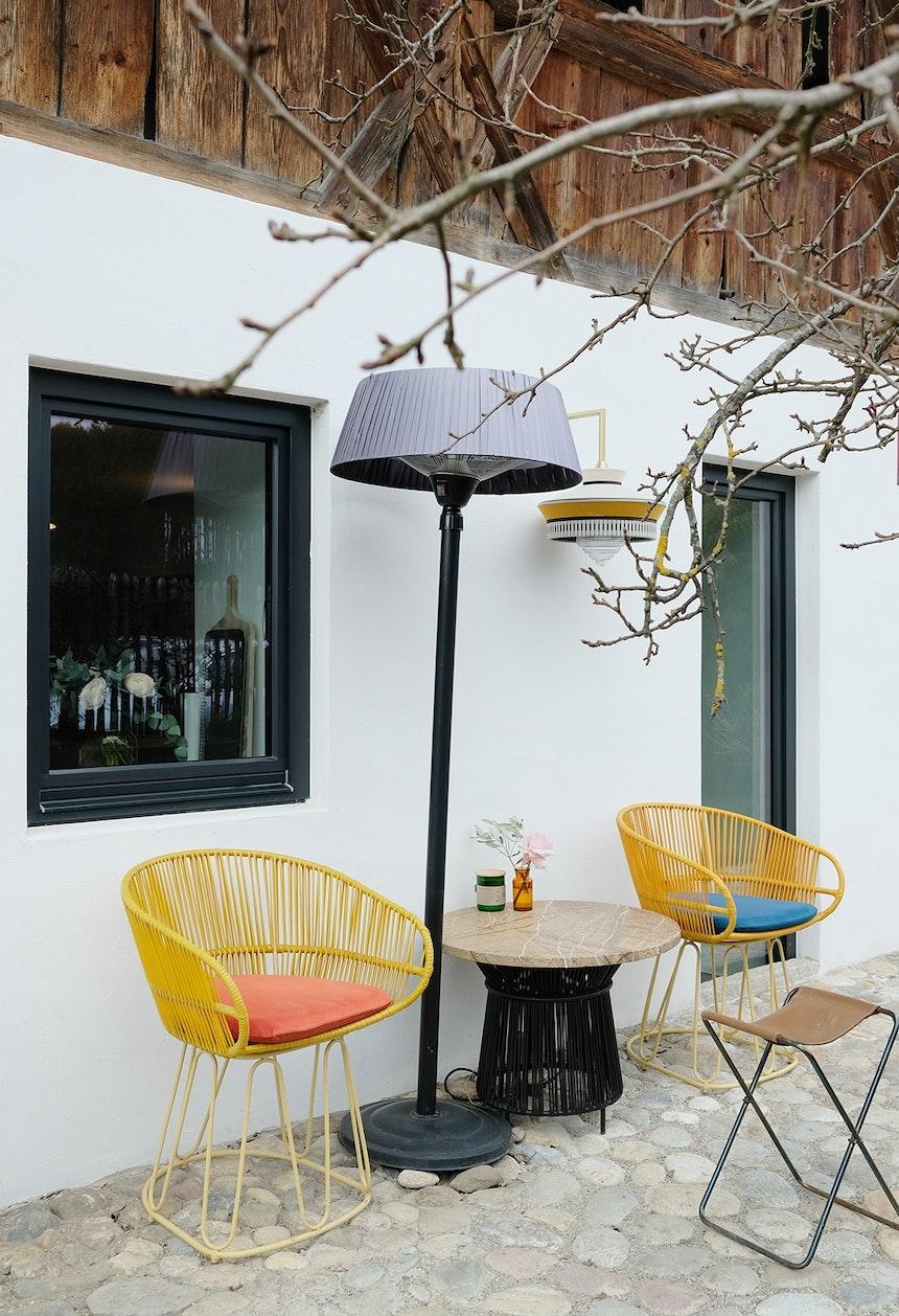 Farbenfroh – Der Sitzplatz hinter dem Haus mit bunten Outdoor-Möbeln (Ames Design), Infrarotheizlampe (blumfeldt) und einer Wandleuchte von Contardi Lighting