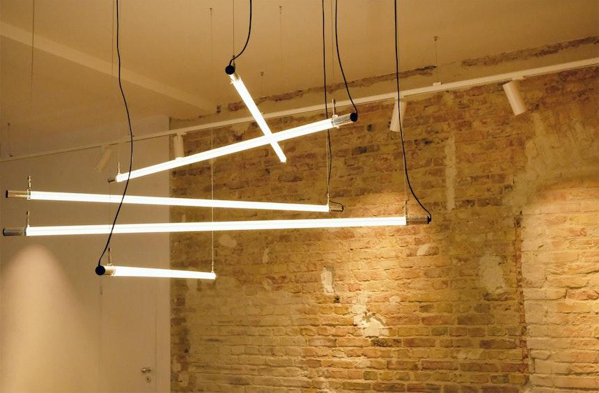 Schöne Kombination – Lampen-Installation aus Neonröhren & rohe Backsteine