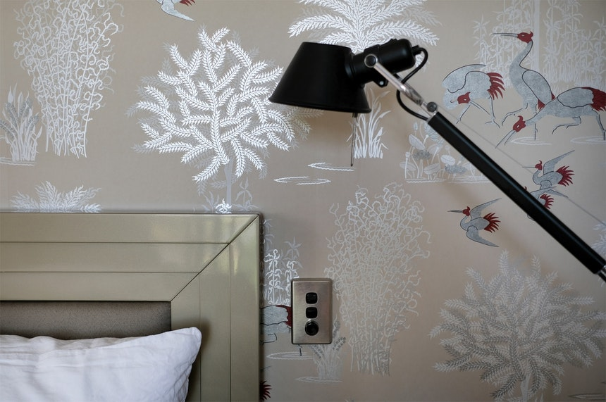 Schlafzimmer mit gemütlichem Bett, Art Déco-Kopfteil, schwarzer Tolomeo (Artemide) und Jagmandir Wallpaper mit silbernen Kranichen (Osborne & Little)