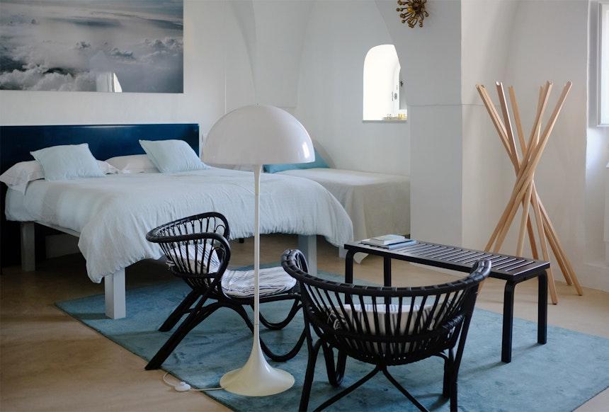 Turmzimmer – schwarze Fox Chairs (SIKA Design), Panthella Stehleuchte (Louis Poulsen) und Sciangai Garderobenständer (Zanotta)