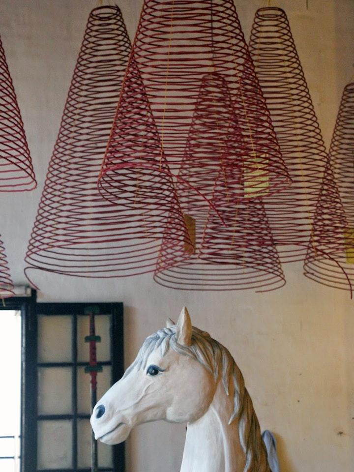 Pferdeskulptur und riesige Räucherspiralen im Juan Công Miéu Tempel