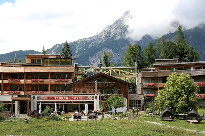 Die ehemalige Skihütte, eingerahmt von den Holzhäusern und verbunden durch die Brücke