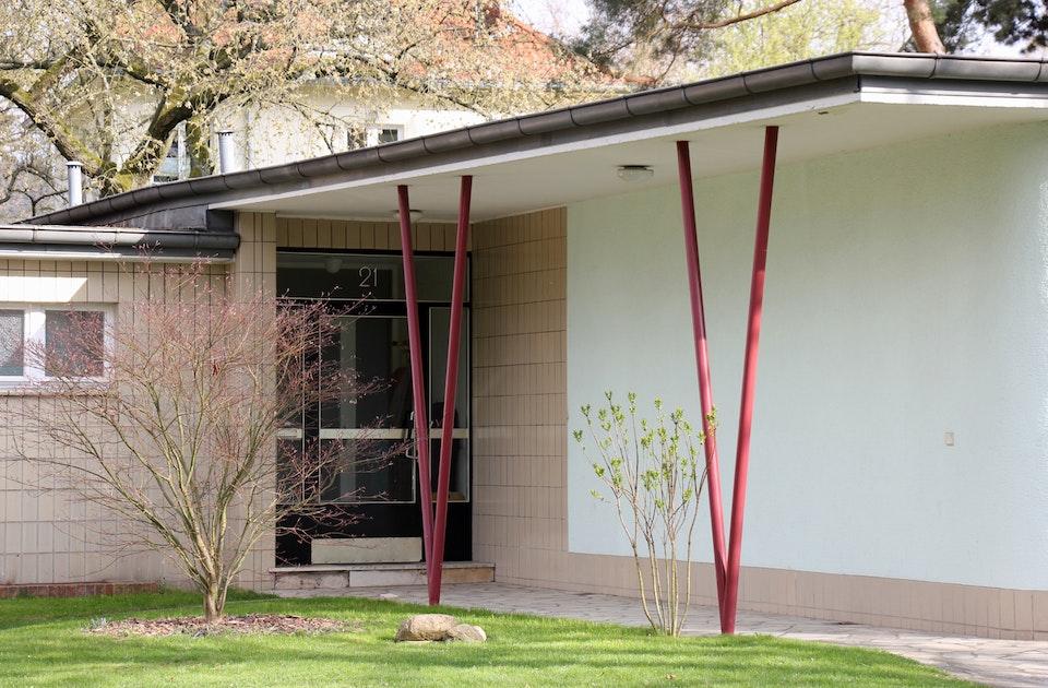 Hochrechteckige (glasierte) Klinkerverkleidung des Eingangsbereichs und Sockels, farbige Stahlstützen