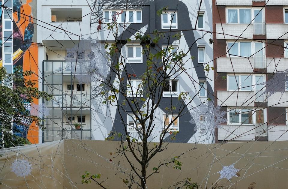 »Untitled«, Nespoon, Spinnennetz aus Häkeldeckchen vor »One Wall«-Fassade von David de la Mano