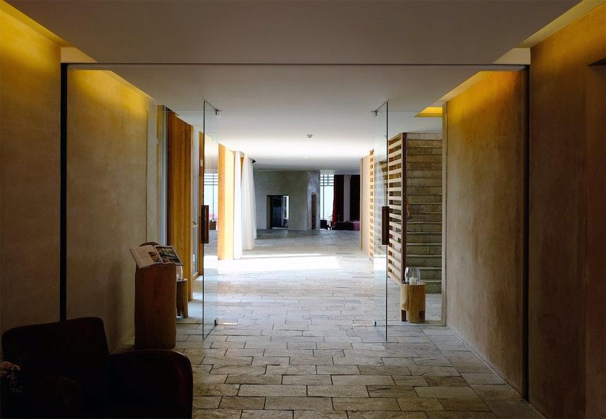 Der Eingangsbereich empfängt die Gäste mit großzügiger Weite, Licht und Naturmaterialien