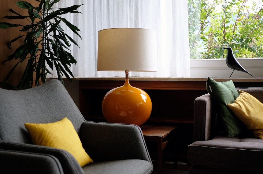 Kugel-Lotte in Orange und viele bunte Kissen (Svenskt Tenn) im Wohnzimmer der ersten Etage, Eames House Bird (Vitra)