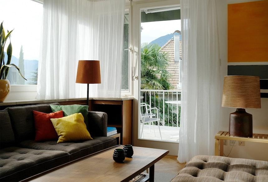 Schöne Aussicht(en) – Sofa (Angelucci, Melbourne), Alvar Aalto-Bank (Artek) und Blick vom Balkon in die Natur